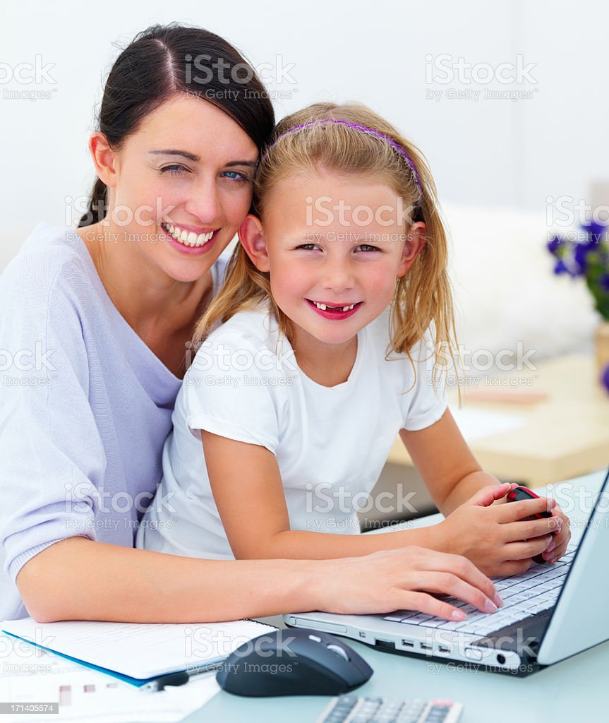 Smiling young mother and daughter sitting together by laptop royalty-free stock photo