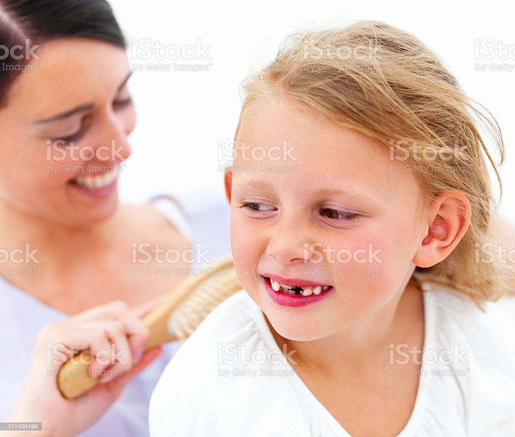 Smiling young mother combing hair of daughter royalty-free stock photo