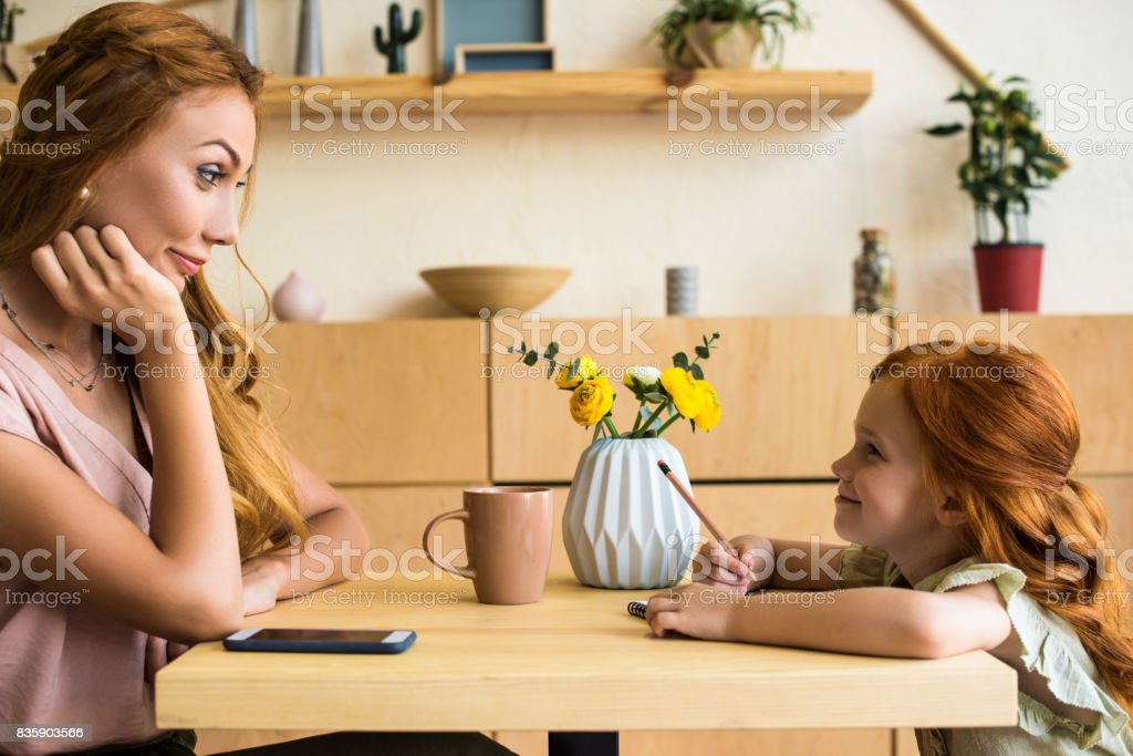 smiling young mother looking at cute little daughter drawing with pencil in cafe stock photo