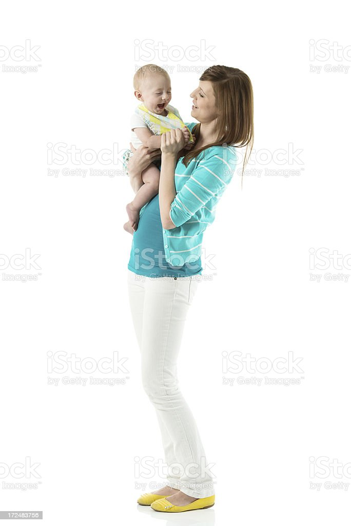 Smiling young mother playing with her baby royalty-free stock photo