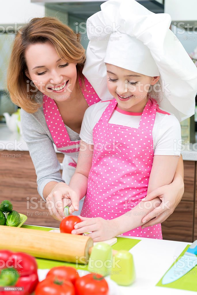Smiling young mother with daughter cooking. stock photo