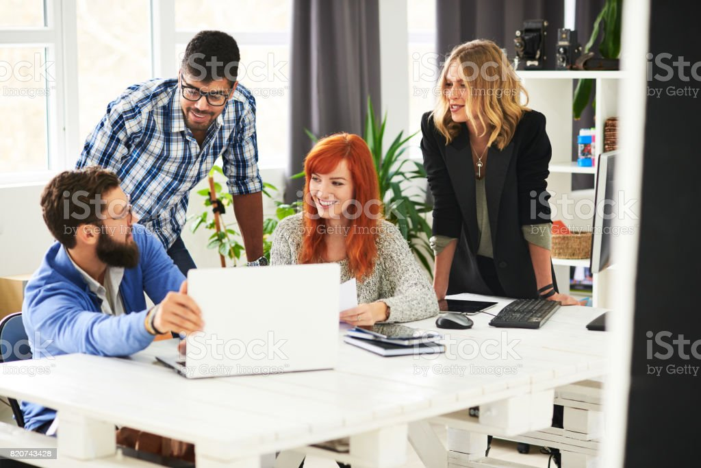 Smiling young people at the office stock photo