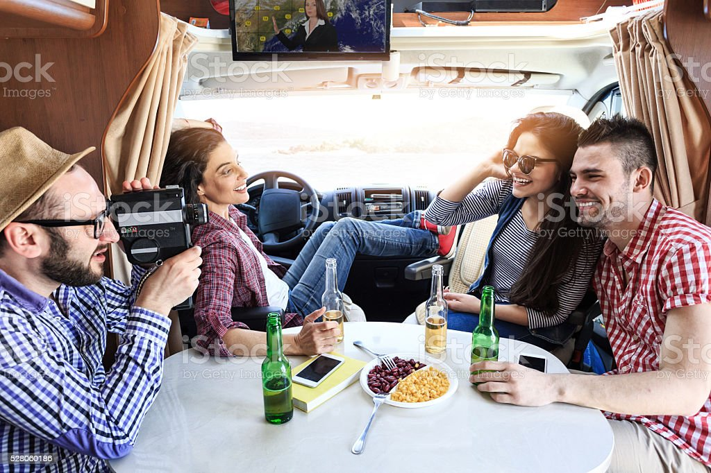Smiling young people having fun inside of a camper stock photo