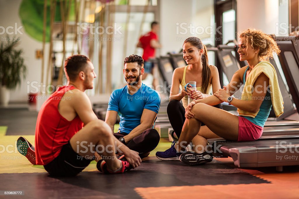 Smiling young people relaxing in a gym and communicating. stock photo