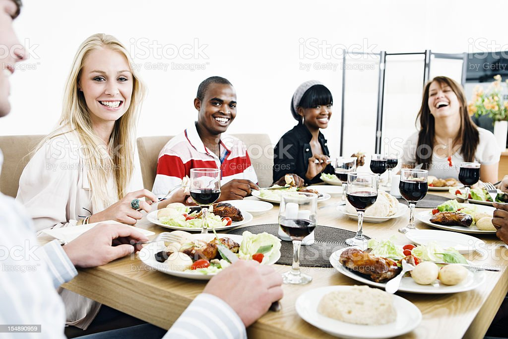 Smiling young people share a meal royalty-free stock photo