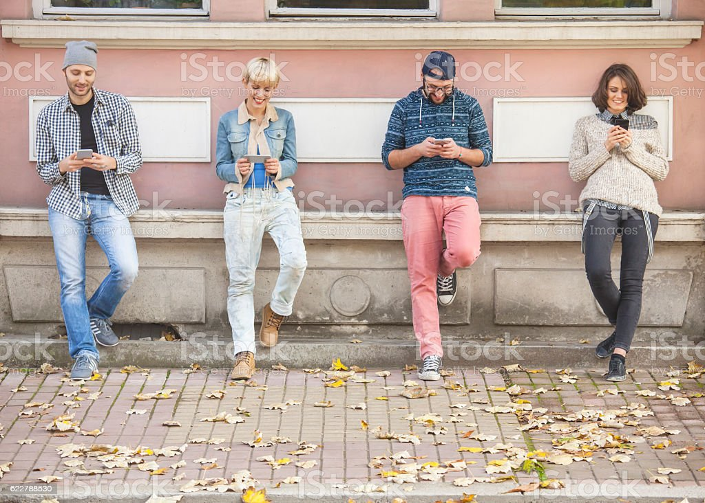 Smiling young people using smart phones stock photo