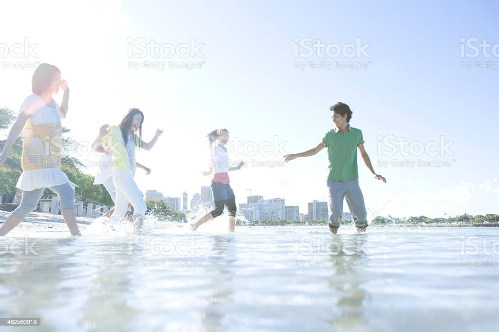 Smiling young people walk into sea royalty-free stock photo