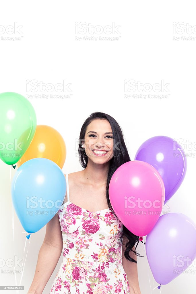 Smiling Young Pretty Brunette Woman holding Colorful Balloons stock photo