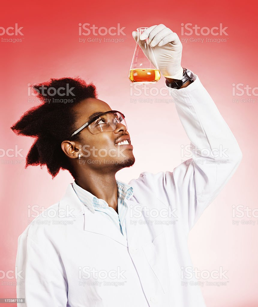 Smiling young scientist looks up at flask of yellow fluid royalty-free stock photo