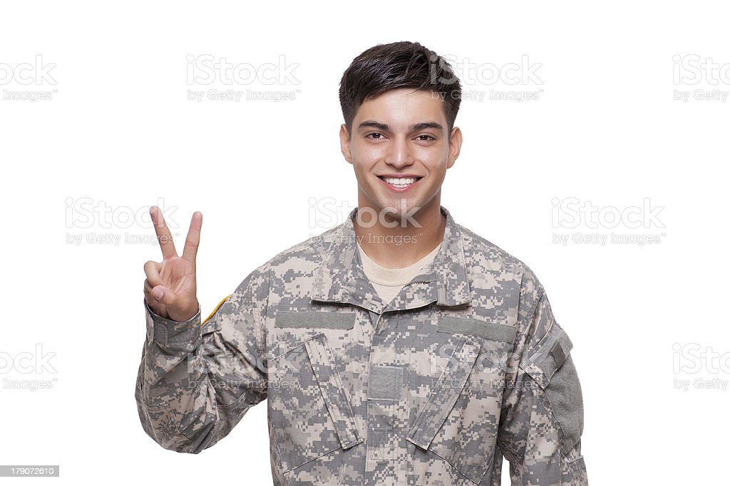 Smiling young soldier gesturing peace sign royalty-free stock photo