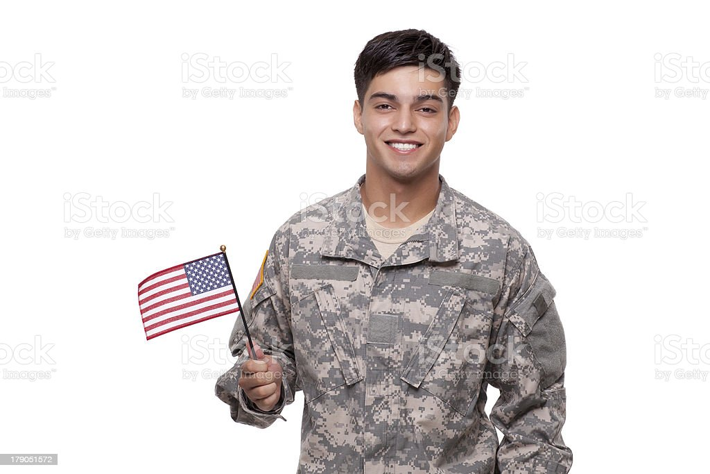 Smiling young soldier posing with an American flag royalty-free stock photo