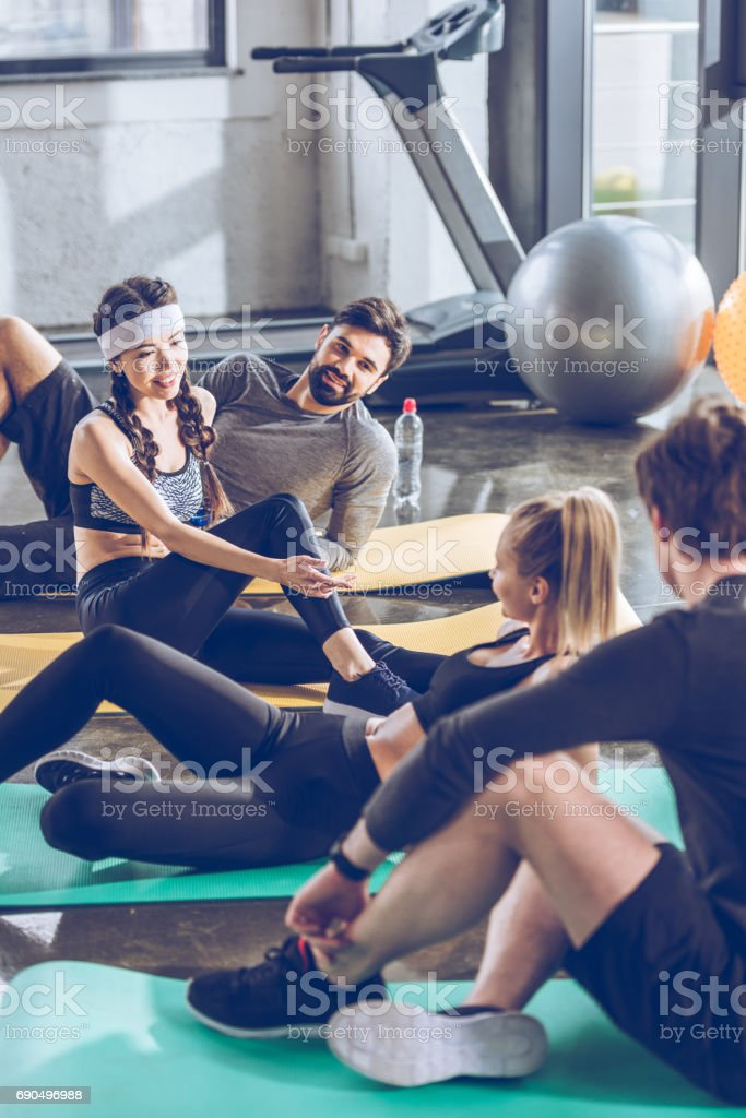 Smiling young sporty people lying on yoga mats and talking while exercising at the gym stock photo