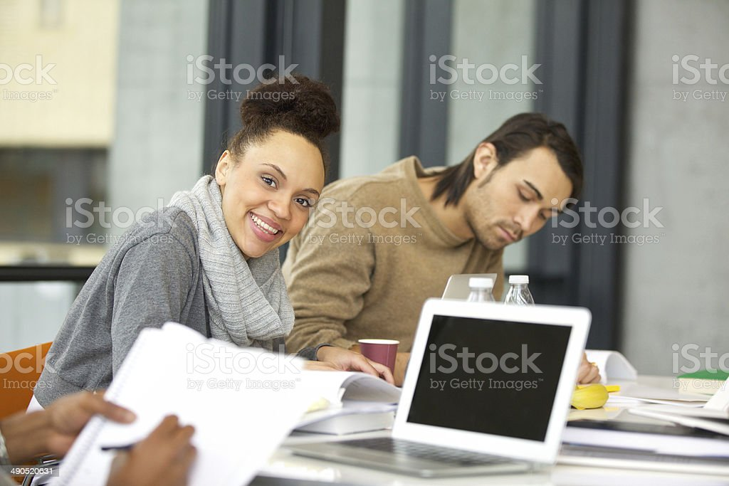 Smiling young student studying in the college library stock photo