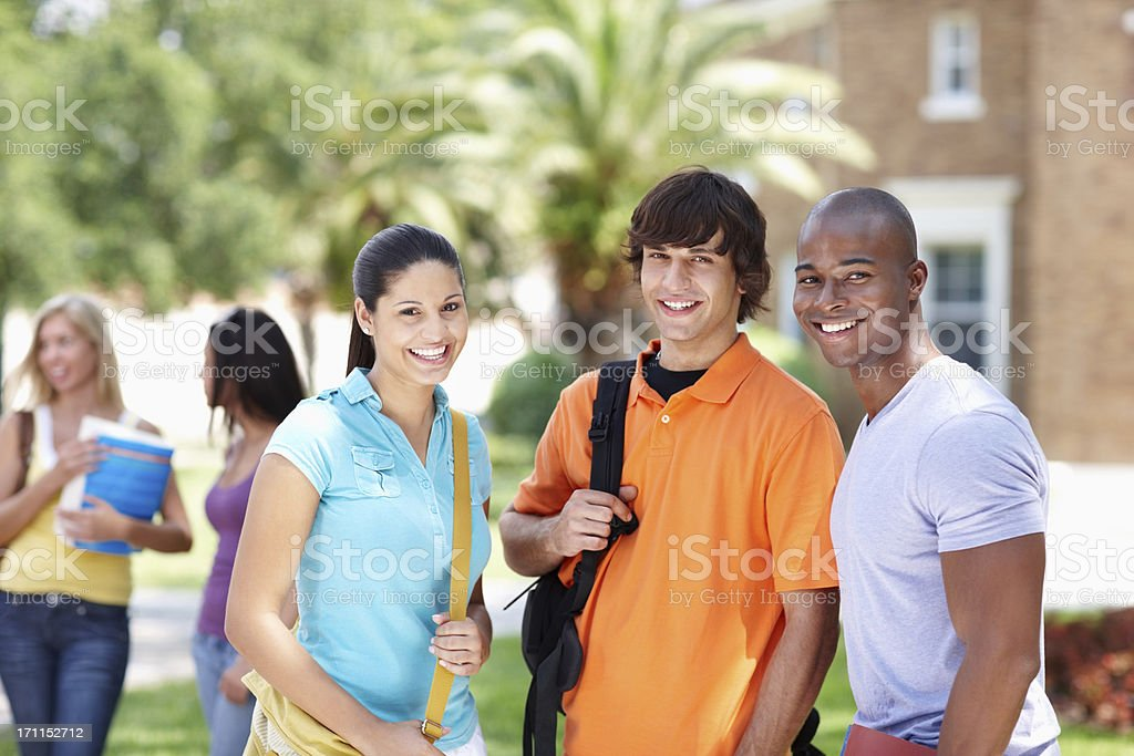 Smiling young students standing at college campus royalty-free stock photo