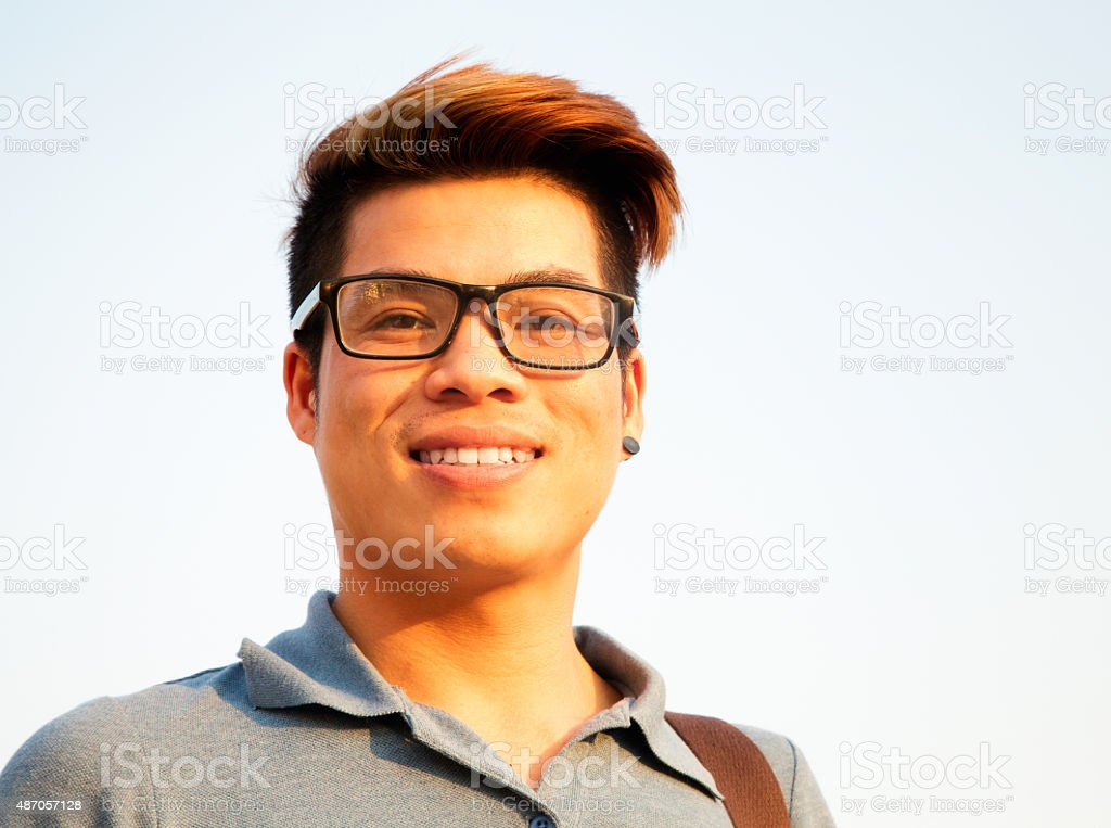 Smiling young Vietnamese male student wearing glasses stock photo