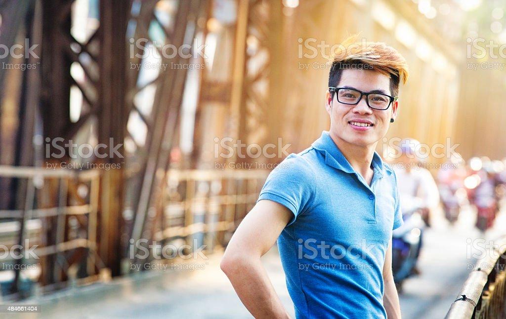 Smiling young Vietnamese man on Long Bien bridge turning stock photo