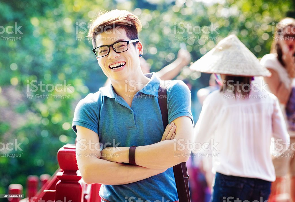Smiling young Vietnamese tourist laughing arms crossed visiting Hanoi stock photo