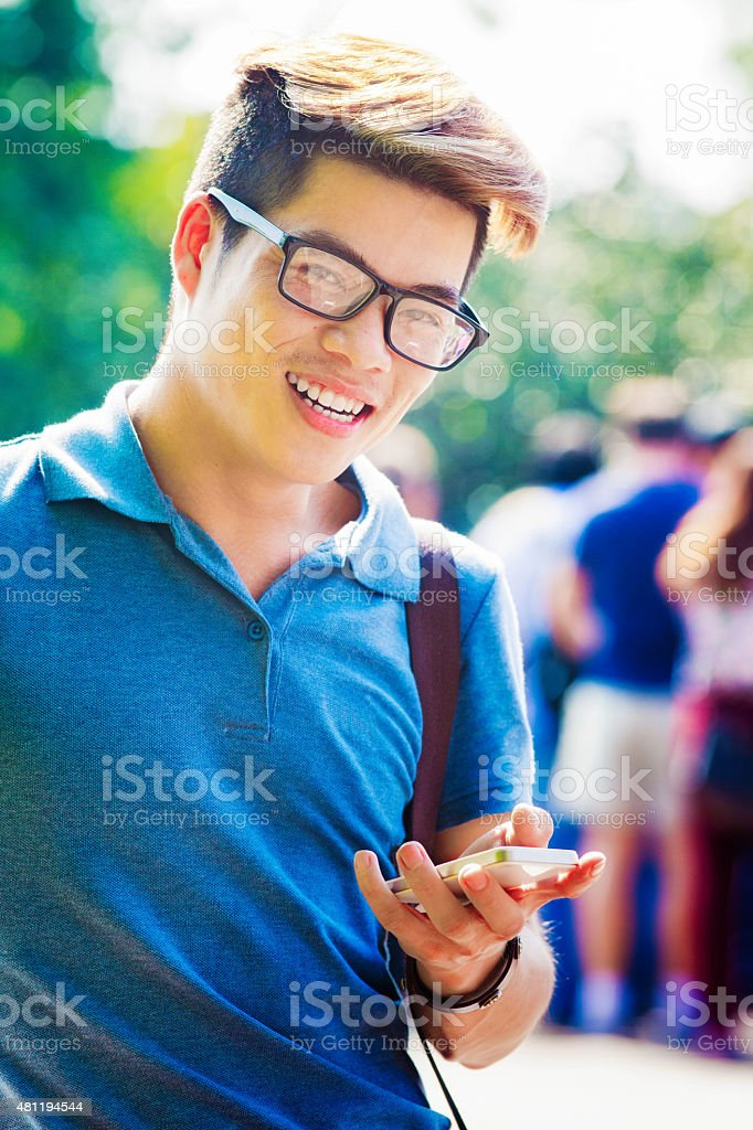 Smiling young Vietnamese tourist looking up smiling from phone stock photo
