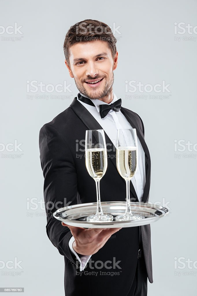 Smiling young waiter in tuxedo offers you glass of champagne stock photo