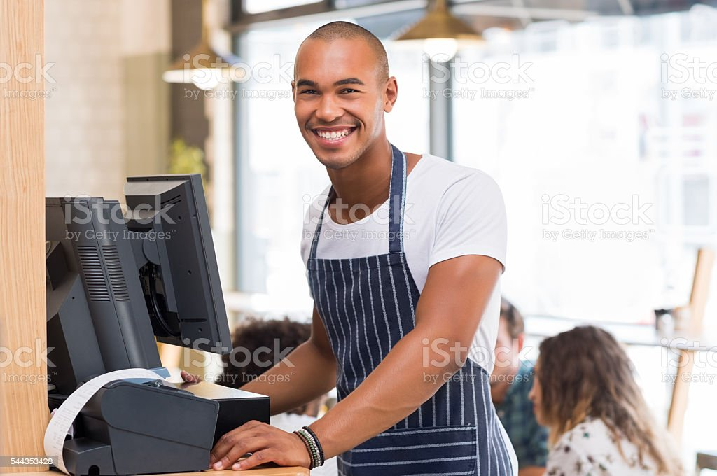 Smiling young waiter stock photo