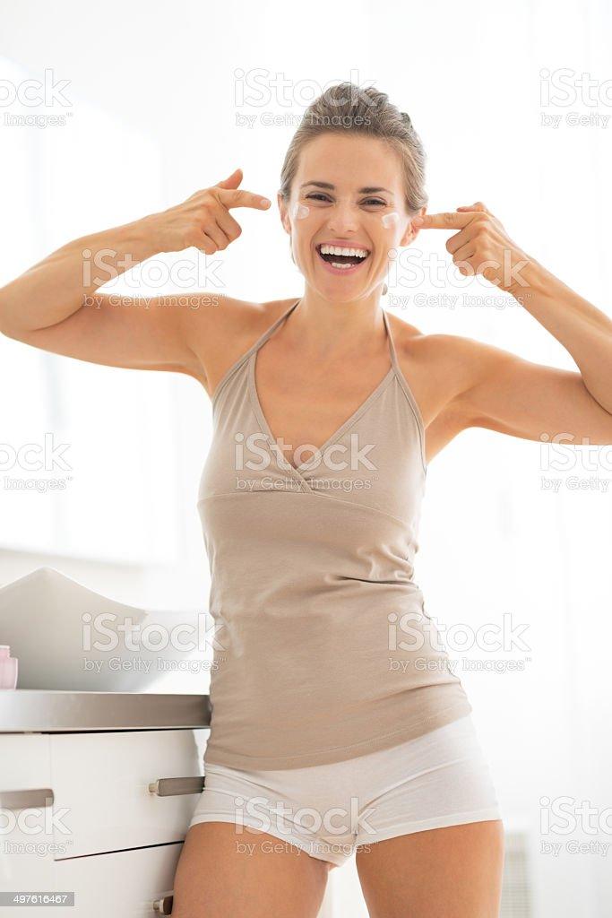 smiling young woman applying cream in bathroom royalty-free stock photo