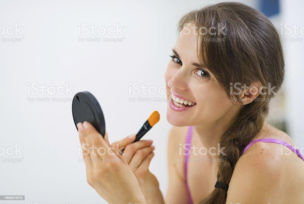 smiling young woman applying makeup stock photo