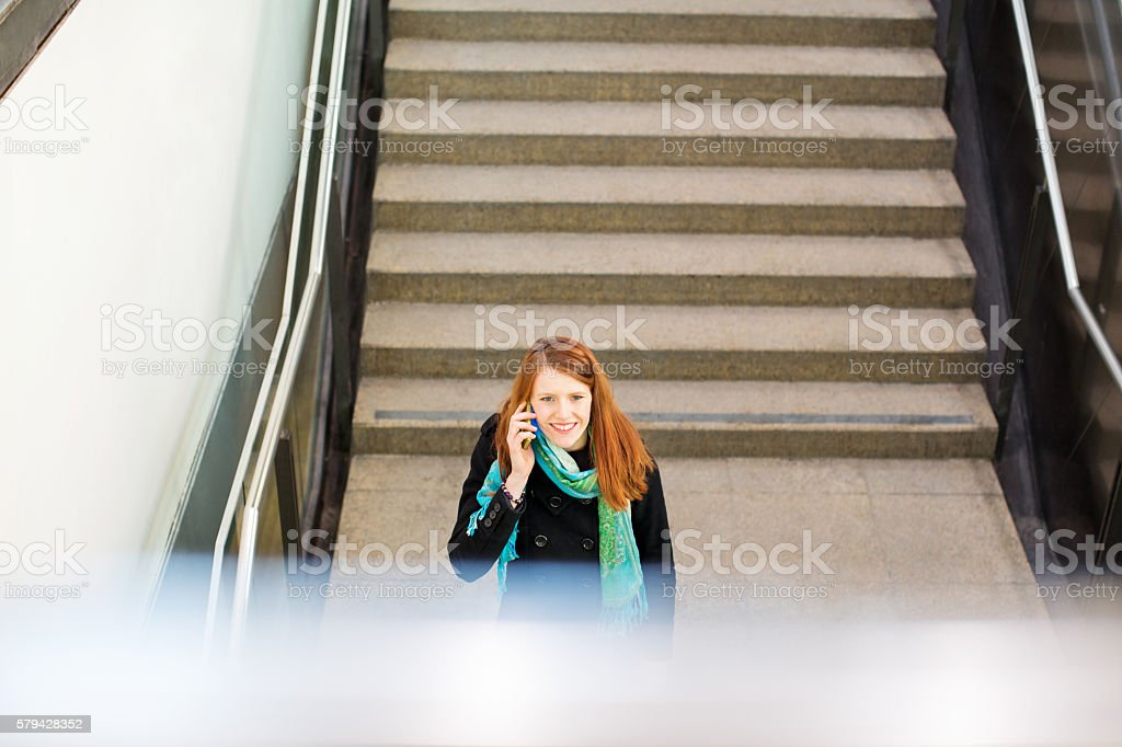 Smiling young woman at subway station stock photo