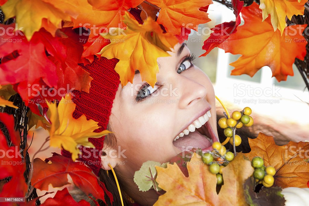 Smiling young woman behind autumn wreath royalty-free stock photo