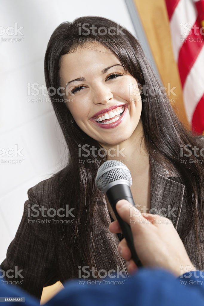 Smiling Young Woman Being Interviewed With Microphone royalty-free stock photo