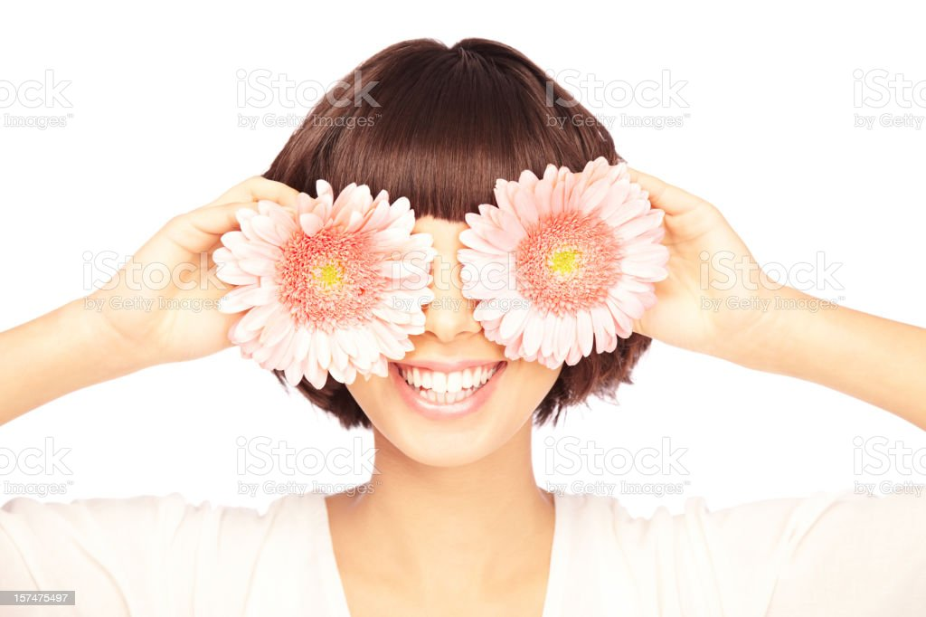 Smiling Young Woman Covering her eyes with Flowers stock photo