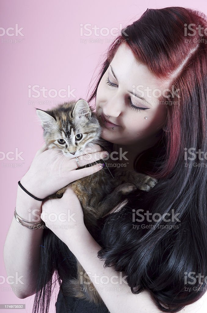 Smiling young woman cuddling kitten royalty-free stock photo