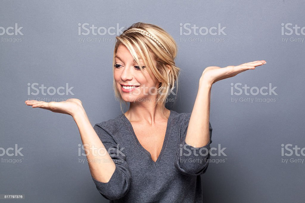 smiling young woman displaying empty hands to weight products stock photo