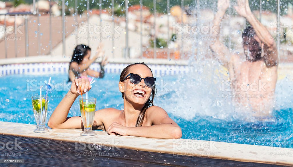 Smiling young woman drinking cocktails at swimming pool stock photo