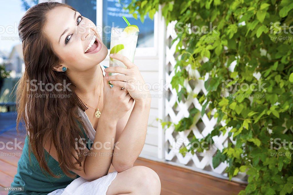 Smiling young woman drinking lemonade royalty-free stock photo