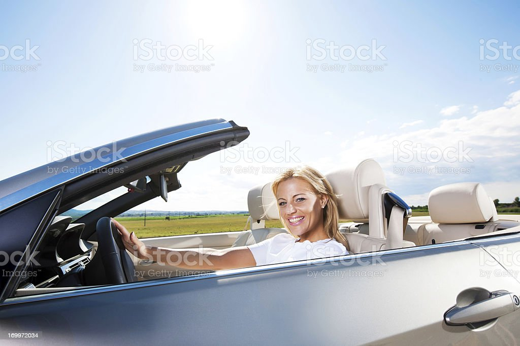 Smiling young woman driving a car royalty-free stock photo