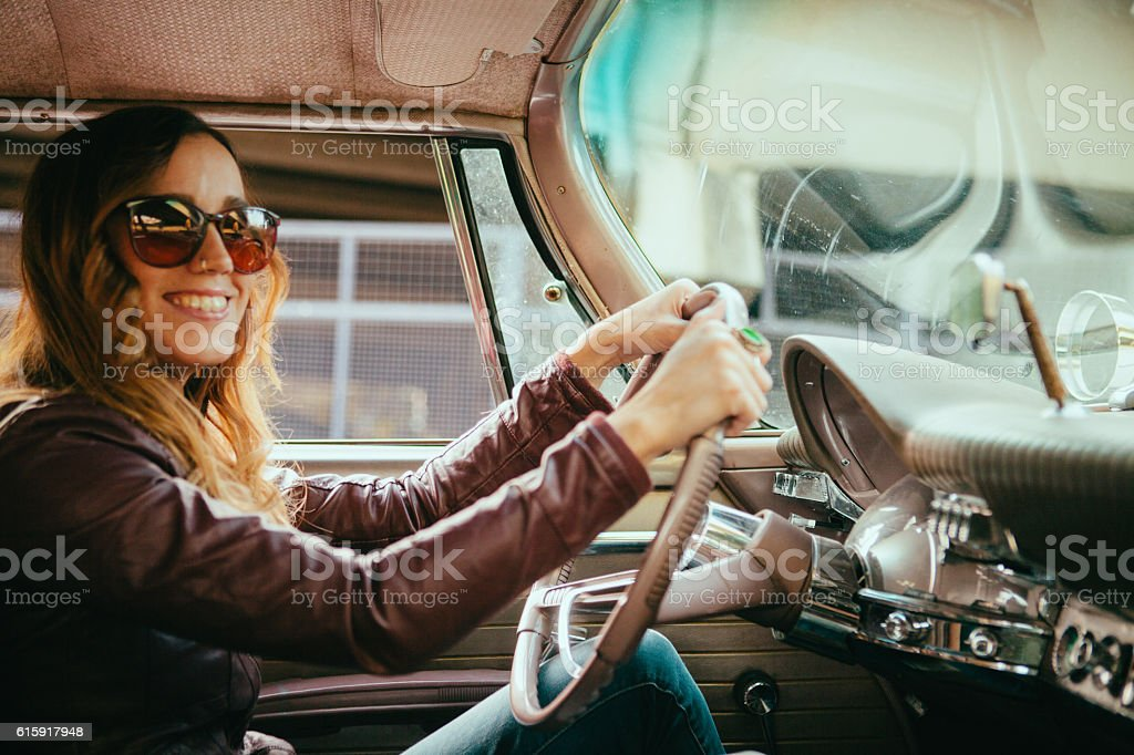 Smiling Young Woman Driving Vintage American Car stock photo