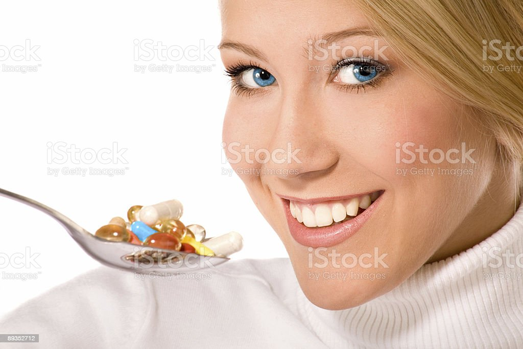 Smiling young woman eating  a lot of pills on  spoon. royalty-free stock photo