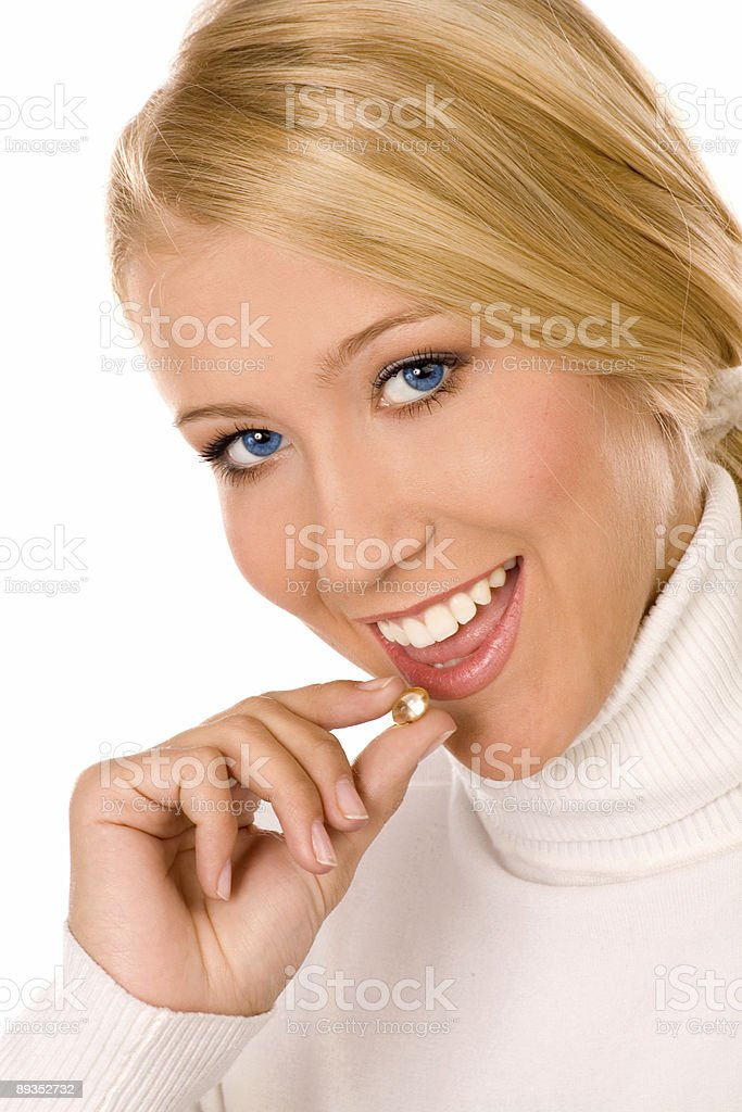 Smiling young woman eating a pill . royalty-free stock photo