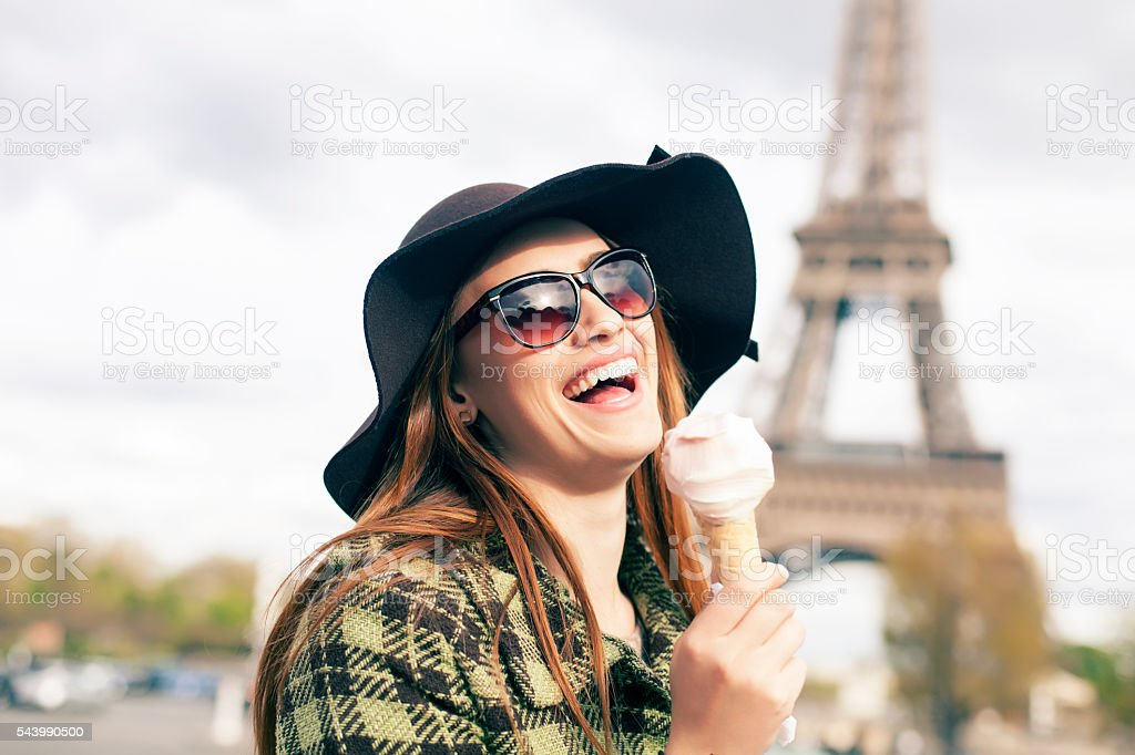 Smiling young woman eating ice cream at Eiffel Tower stock photo