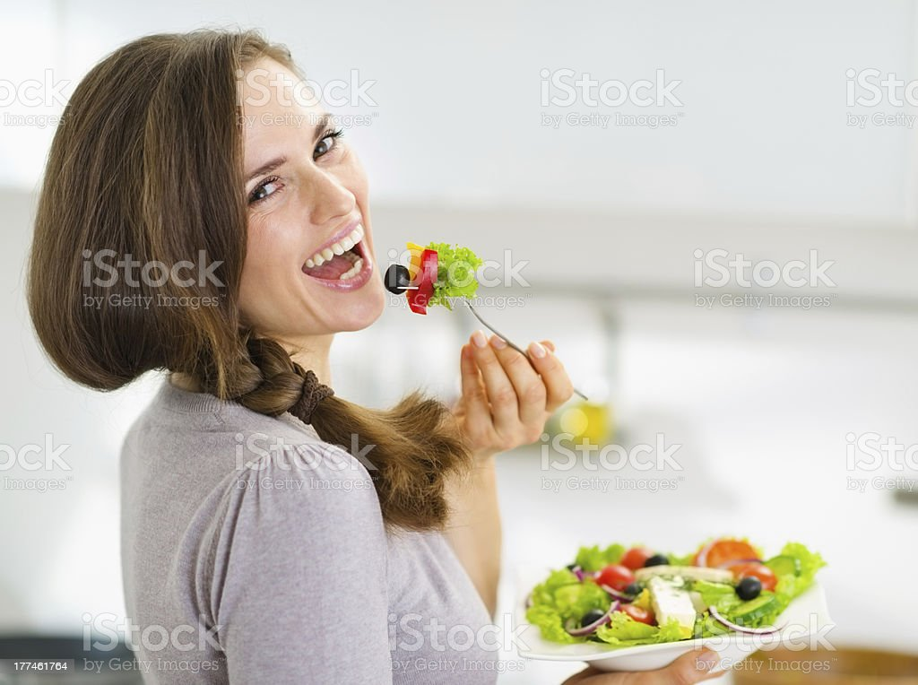 Smiling young woman eating salad in modern kitchen stock photo
