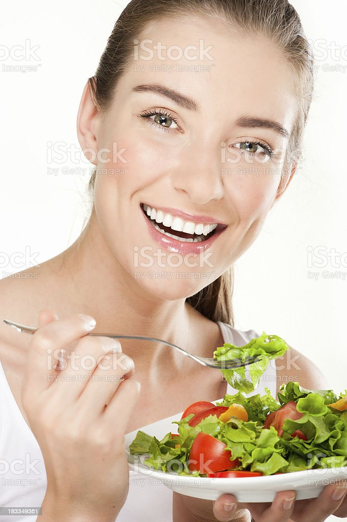 smiling young woman eats salad royalty-free stock photo