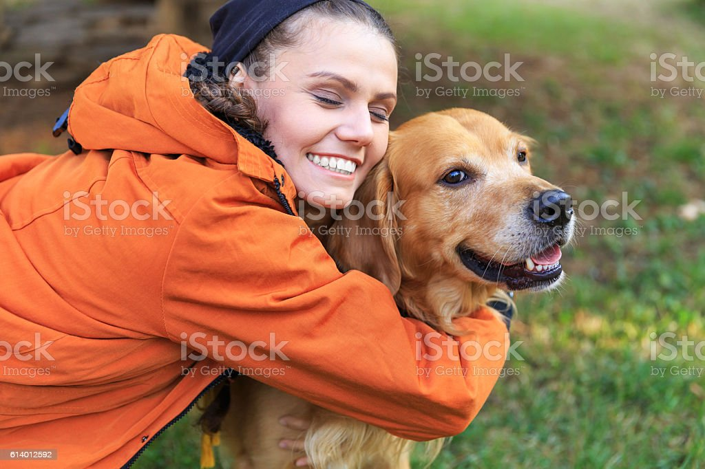 Smiling young woman embracing a dog stock photo