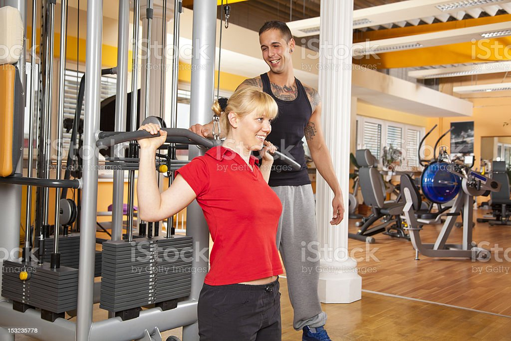 smiling young woman exercising in gym with trainer stock photo