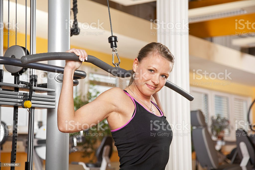 smiling young woman exercising latissimus dorsi in gym stock photo
