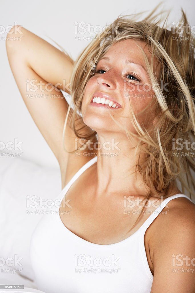 Smiling young woman flipping her hair in bed royalty-free stock photo