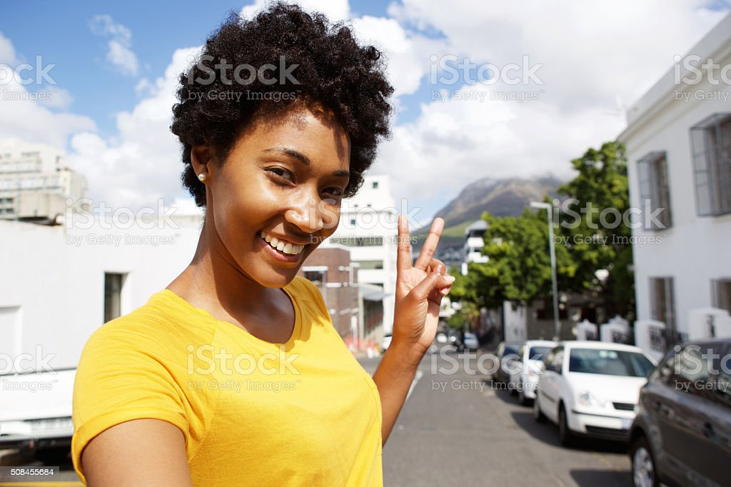 Smiling young woman gesturing peace sign stock photo