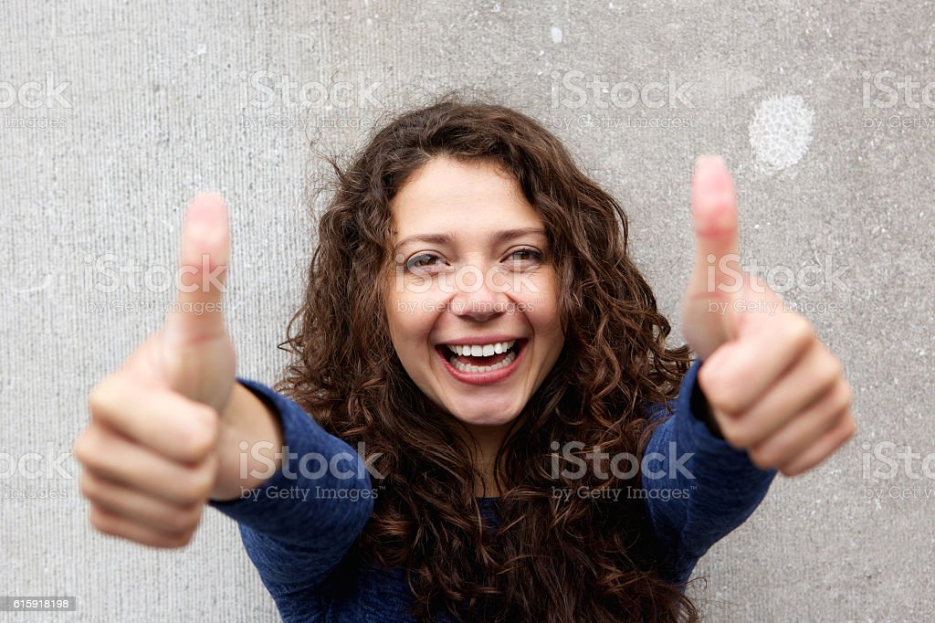 Smiling young woman giving thumbs ups stock photo
