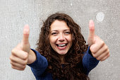 Smiling young woman giving thumbs ups