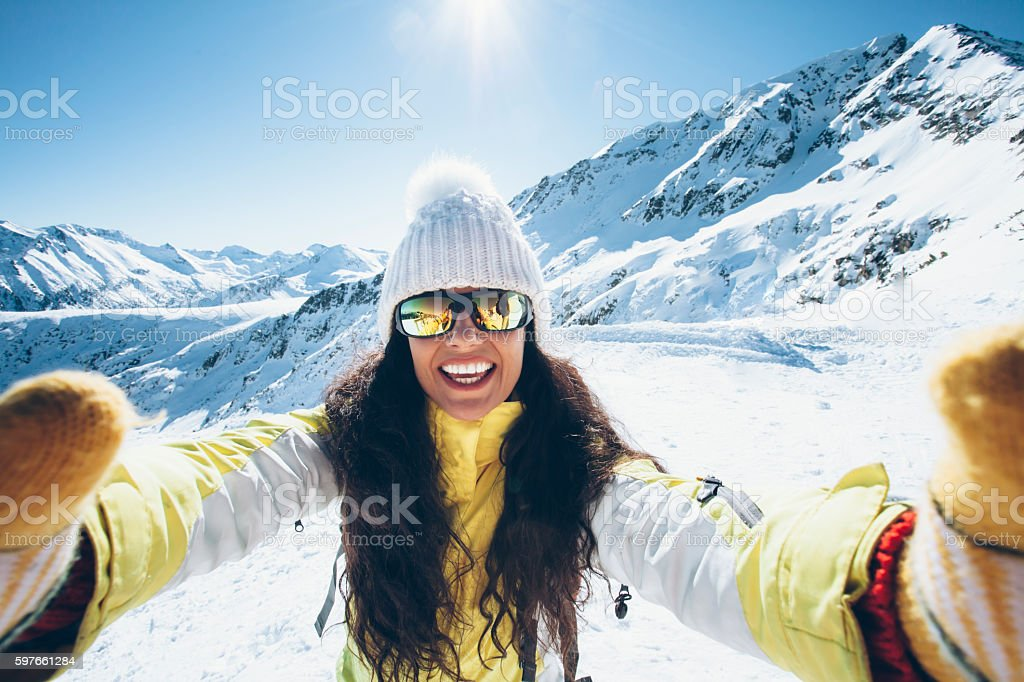 Smiling young woman having fun in the snow mountain stock photo