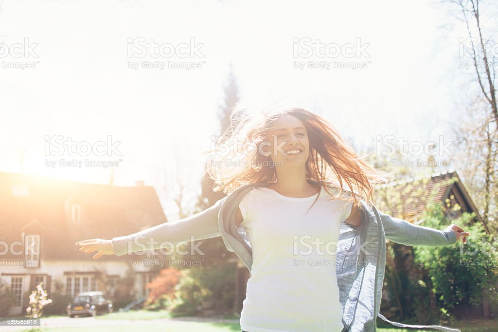 Smiling young woman having fun outdoors stock photo